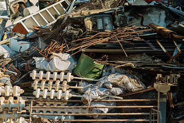 Storage of scrap metal. Piles of scrap metal for recycling in an open-air warehouse. Collection of recyclable materials for industry